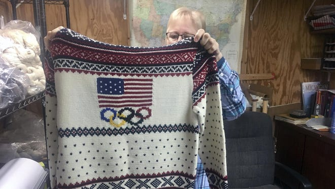 Debbie McDermott holding up the back side of a Ralph Lauren sweater in East Jordan, Mich., that athletes wore for the 2014 Winter Olympics closing ceremony. The sweater was made using Shepherd's Wool, one of Stonehedge Fiber Mill's yarn lines.