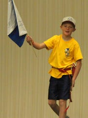 """A member of the """"Mustard"""" team looks at grabbing an opposing team's flag in an intense game of Capture the Flag at the Cub Scout Investigator's camp on Thursday. The camp was held to teach the scouts life skills as well as introduce them to Cub and Boy Scout life."""