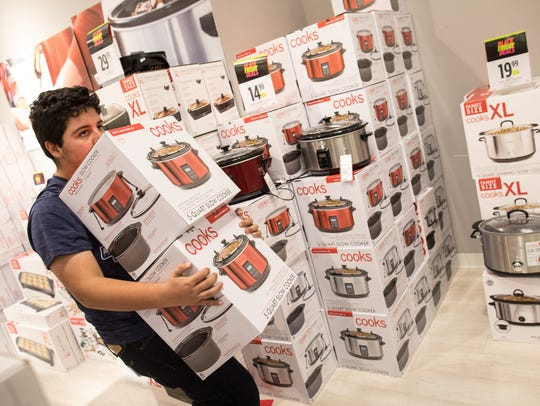Joaquin Haces Garcia carries crock pots through JCPenney