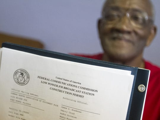 The Rev. Jessie Denson, president of the Dunbar Gospel Association, shows the FCC permit for radio station STAR-FM in 2015.