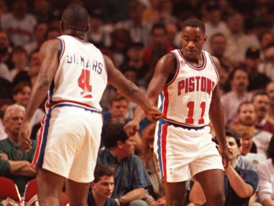 Detroit's Isiah Thomas gets a friendly well done from his court buddy Joe Dumars as Thomas heads to the bench for a break against Orlando.