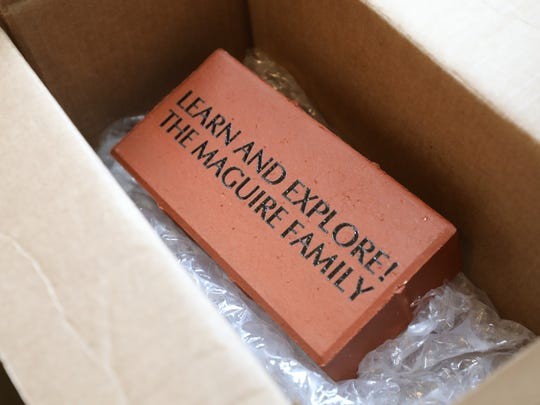 A sample fundraising brick is pictured as a fundraiser