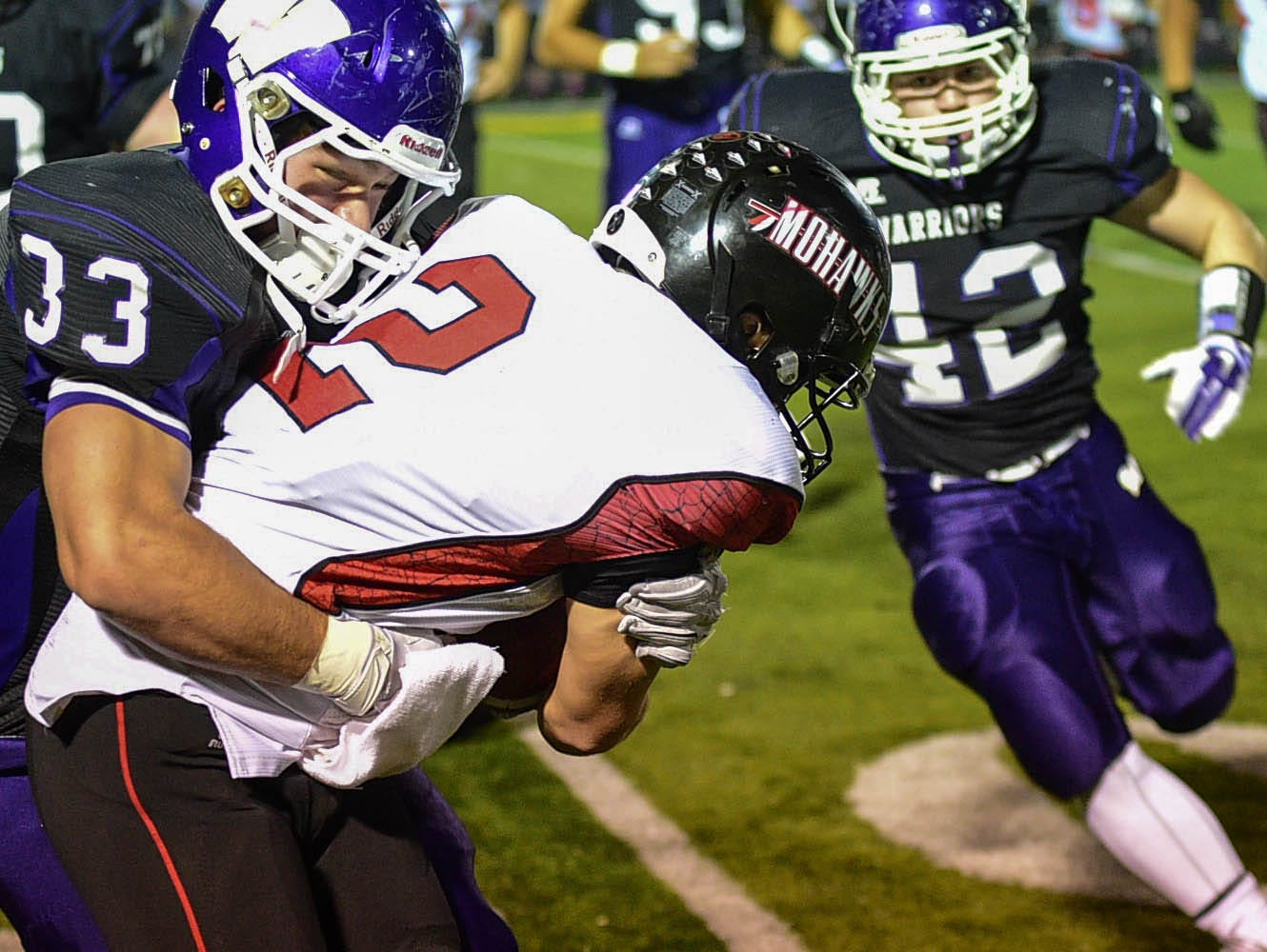 Waukee's linebacker Kyle Boulanger (33) manages to stop Mason City's quarterback Austin Hemmen (2) after he scrambled out of the backfield and gained several yards during the first half of the game at Waukee Stadium on Friday, Oct. 24, 2014.