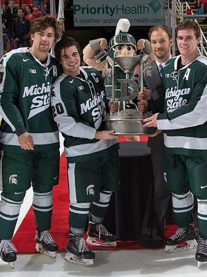 "From left, MSU seniors Justin Hoomaian, Michael Ferrantino and Travis Walsh pose with the ""Iron D"" trophy after defeating Michigan in the ""Dual in the D"" on Feb. 5 at Joe Louis Arena."