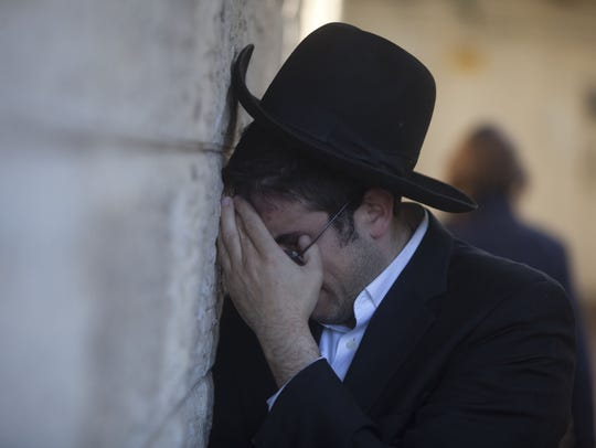 An Ultra Orthodox Jewish man cries during the funeral
