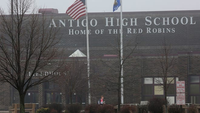 A student crosses below two flags while entering Antigo High School on Monday, April 25, 2016, less than two days after a deadly shooting at the high school prom Saturday, April 23, 2016.