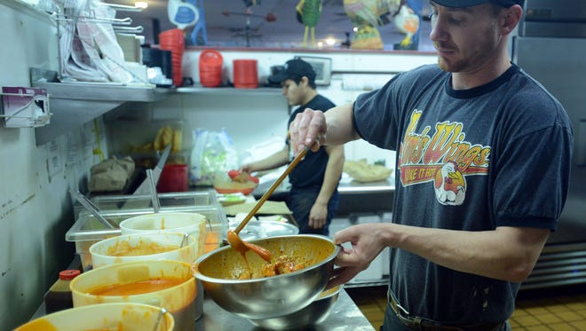 Brain Hall, pours hot sauce on chicken wings at Jim's Wings on East Elizabeth Street.