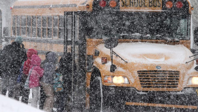 Elementary school students board a bus in the snow.