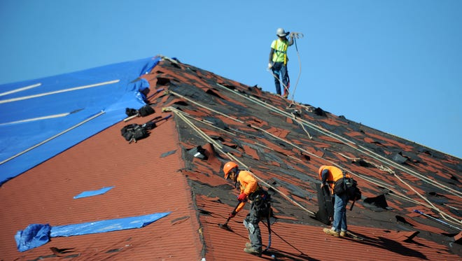 Construction workers fix a damaged roof from the EF3 tornado that hit William Carey University on Saturday.