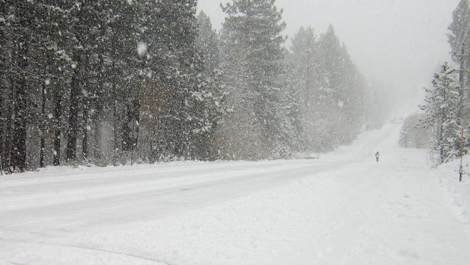 A pedestrian walks in the snow along Ski Run Boulevard in South Lake Tahoe, Calif., Tuesday, Nov. 10, 2015. The wet-weather system heading moving across California from the Pacific to the Sierra Nevada brought cool, wet weather to low-lying areas and snow to the mountains. (Caitlin Row/Tahoe Daily Tribune via AP) MANDATORY CREDIT