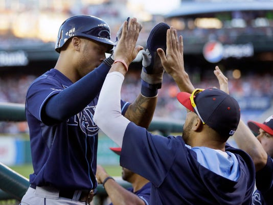Tampa Bay Rays' Desmond Jennings, left, is met in the dugout after scoring from first on a double by teammate Ben Zobrist during the fifth inning of a baseball game against the Detroit Tigers in Detroit, Friday, July 4, 2014. (AP Photo/Carlos Osorio)