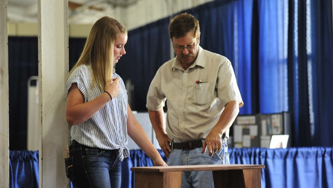 Allison Scott, a sophomore at Wynford High School, shows her FFA woodworking project to judge Tom Daiber on Saturday at the Crawford County Fair.