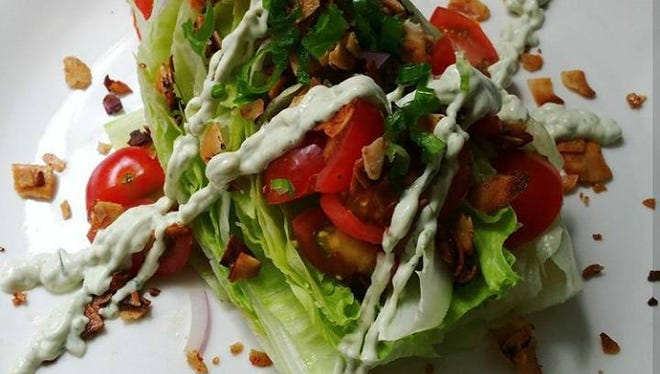 A Wedge Salad contains iceberg lettuce topped with coconut bacon, tomatoes, red onion, chives and a cashew tahini blue cheese dressing.