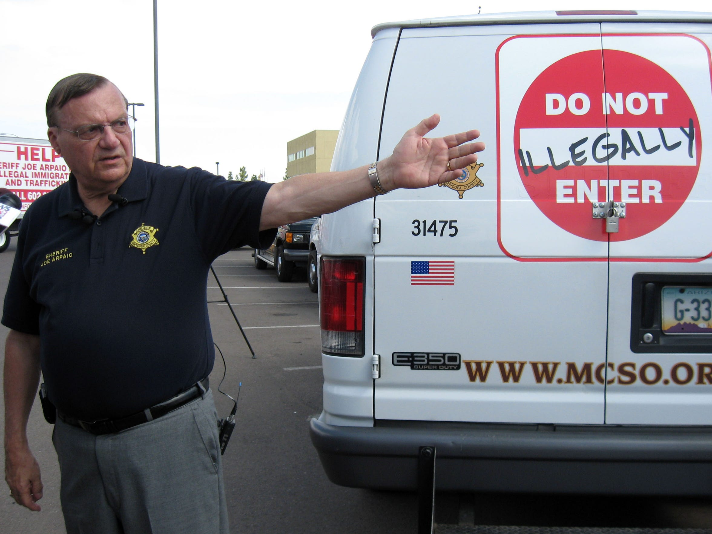 Arpaio shows off one of several vehicles advertising his anti-illegal-immigration hotline in 2007.