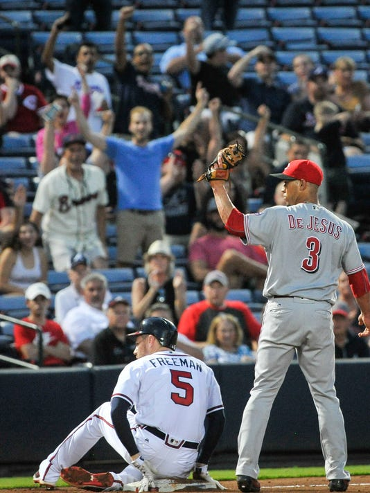 Atlanta Braves' Freddie Freeman (5) and Cincinnati Reds shortstop Ivan De Jesus (3) look to the call from the third base umpire as Freeman triples on a line drive to right field during the fourth inning of a baseball game, Wednesday, June 15, 2016, in Atlanta. (AP Photo/John Amis)