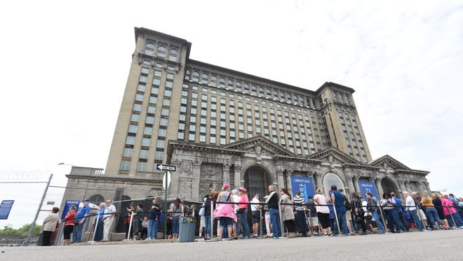 Hundreds of people wait in line outside the Michigan tours of the station during an open house on Friday, June 22, 2108 in Detroit.