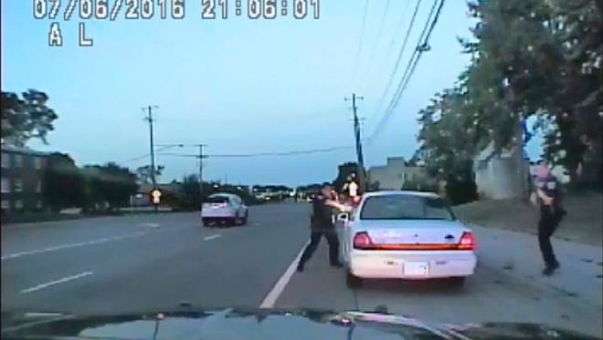 In this image made from July 6, 2016, video captured by a camera in the squad car of St. Anthony Police officer Jeronimo Yanez, the Minnesota police officer shoots at Philando Castile in the vehicle during a traffic stop in Falcon Heights, Minn. Yanez's backup officer Joseph Kauser is seen standing on the passenger side of the vehicle. The video was made public by the Minnesota Bureau of Criminal Apprehension and the Ramsey County Attorney's Office.
