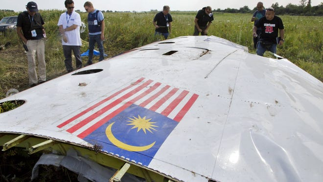 Malaysian investigators examine a piece of the crashed Malaysia Airlines Flight 17 in the village of Petropavlivka, in eastern Ukraine, on July 23, 2014.