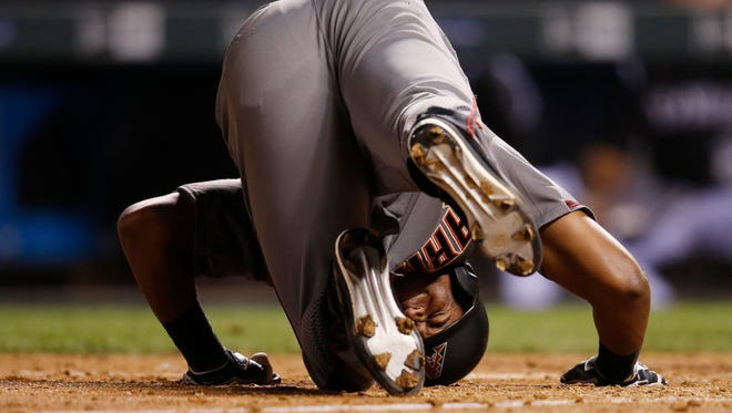 Diamondbacks' Socrates Brito reacts as he falls in the batter's box after fouling off a pitch from Colorado Rockies relief pitcher Justin Miller in the eighth inning of a baseball game Thursday, June 23, 2016, in Denver.