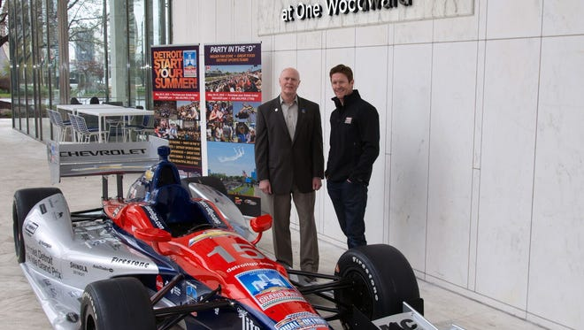 Fifth Third Bank Senior Vice President Jack Riley and race car driver Scott Dixon stand beneath the newly installed Fifth Third Bank at One Woodward sign at the Bank's new regional headquarters.