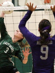 Mescalero's Lauryn Yuzos, right, jumps to block a ball hit by Cloudcroft's Olivia Sealey.
