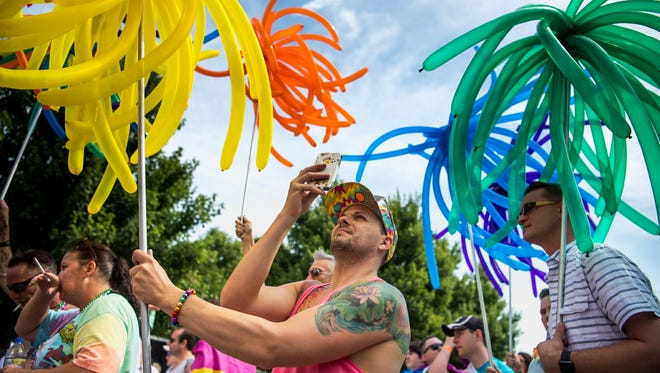 David Westover, of Nashville, takes a picture with his phone while holding balloons during the Nashville Pride Equality Walk in downtown Nashville, Tenn., Saturday, June 24, 2017.