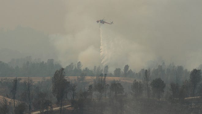 A firefighting helicopter drops water on the Carr Wildfire in Redding, Calif., on July 27, 2018.
