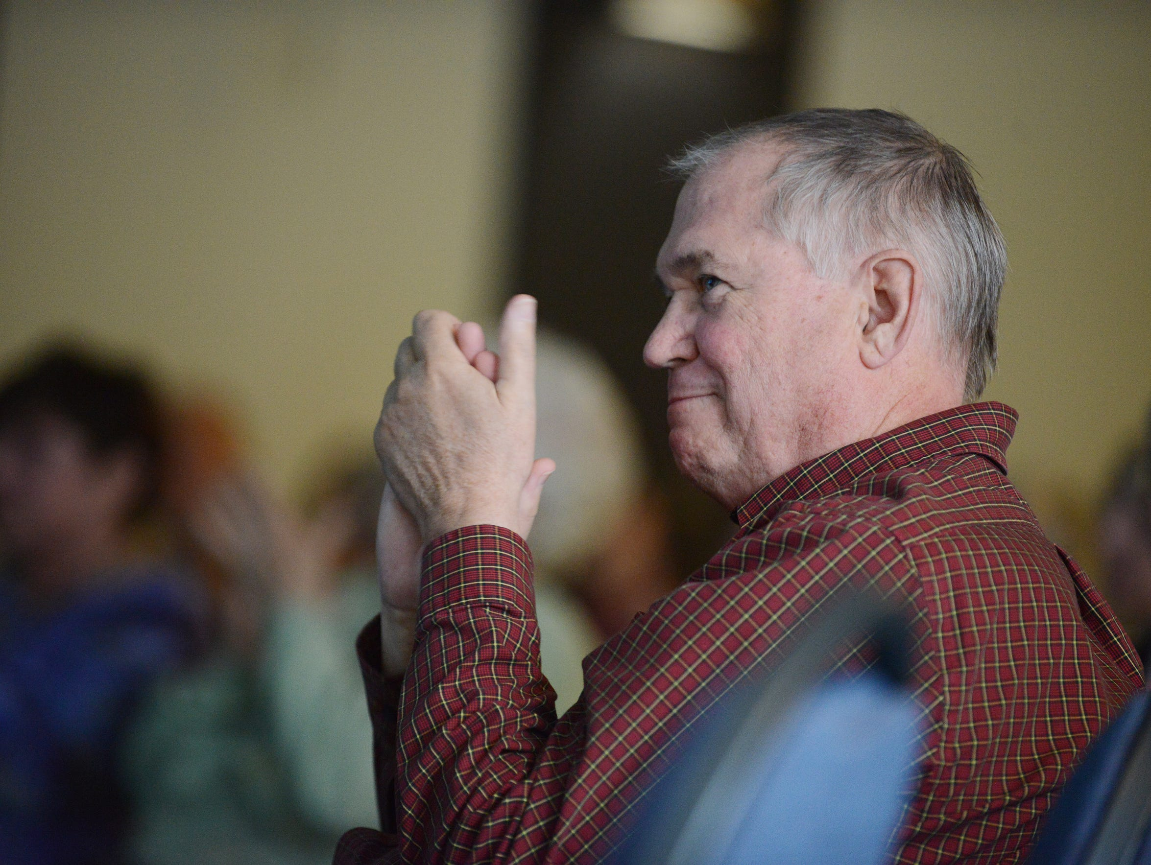 Dr. Peter Rasmussen applauds a fellow speaker during