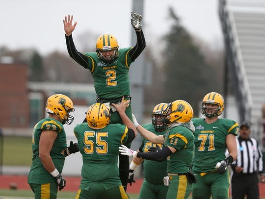 Brockport quarterback Jason Hellwig, 2, is lifted by