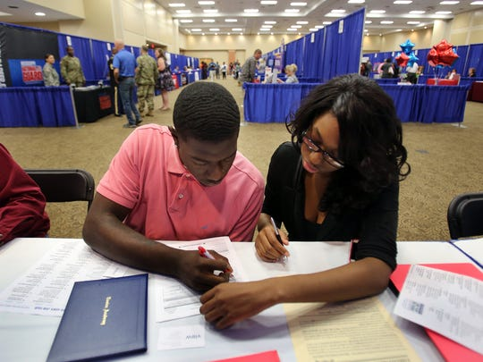 Quintarius Ware (left) filled out job applications, with assistance from his aunt Arkeshia Ware, at a recent job fair at the Lander's Center in the Mississippi suburb of Southaven.