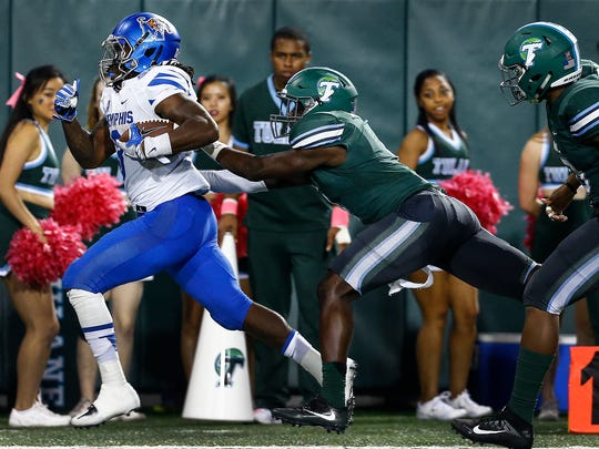 University of Memphis running back Darrell Henderson (left) scrambles past Tulane University defender Will Harper (right) for a 45 yard touchdown run during fourth quarter action at Yulman Stadium in New Orleans.