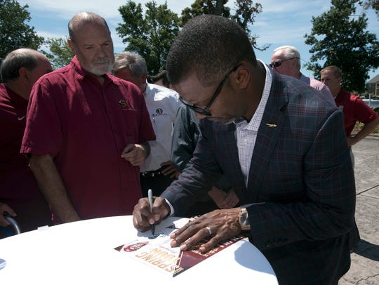 Florida State's Willie Taggart, right, signs autographs
