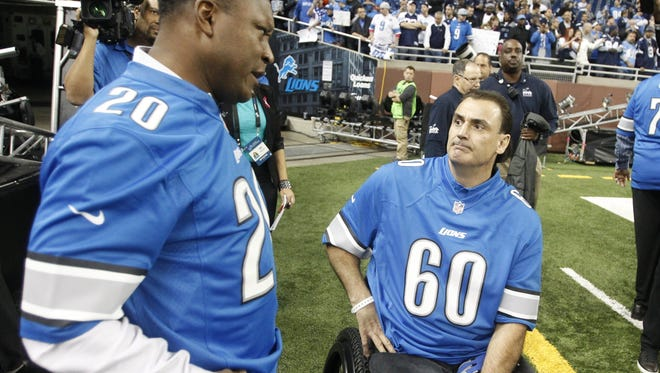 Former Detroit Lions running back Barry Sanders and offensive lineman Mike Utley, right, talk on the sideline before a game against the Dallas Cowboys on Oct. 27, 2013, at Ford Field in Detroit.