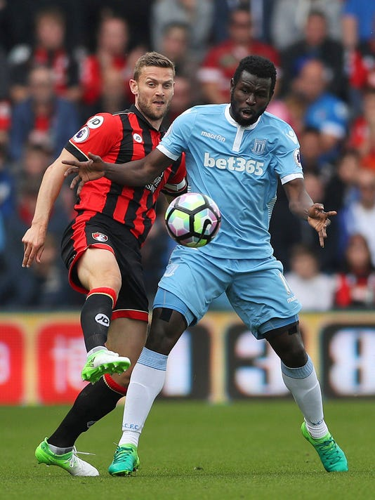 AFC Bournemouth's Simon Francis, left, and Stoke City's Mame Biram Diouf battle for the ball during the Premier League soccer match between AFC Bournemouth and Stoke City at the Vitality Stadium, Bournemouth, England. Saturday May 6, 2017. (John Walton/PA via AP)