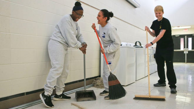 """Fellow cadets Brenizia Hosley, left, and Vianey Valle have a little fun while cleaning up a hallway outside what will be a new dorm room for the Bluegrass ChalleNGe Academy at Fort Knox. """"I'm proud that we finished something we started,"""" said Hosley, about nearing graduation of the 22-week program. At far right is cadre Abby Curtsinger."""