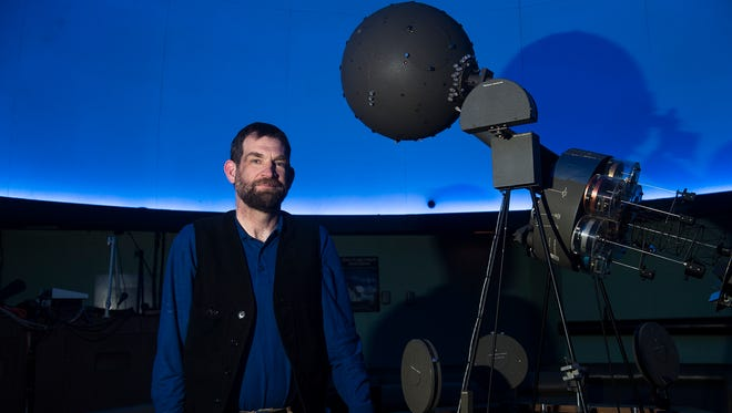 Hatter Planetarium director Ian Clarke stands next to the facility's current projector on Feb. 28, 2016. The planetarium will move to all digitized equipment probably by summer, Clarke said, and the vintage projector will most likely be put on permanent display at Masters Hall.
