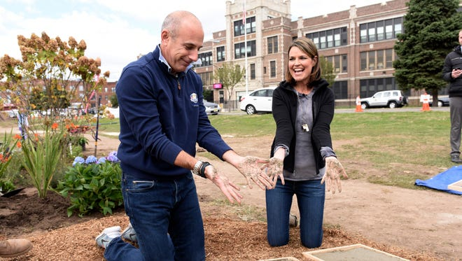 Matt Lauer and Savannah Guthrie of the 'Today' show make handprints in mosaic steppingstones that lead to the butterfly garden at a playground in Passaic, N.J.