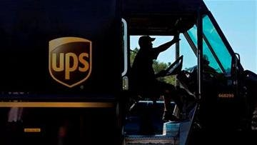 A UPS truck driver enters a company warehouse.