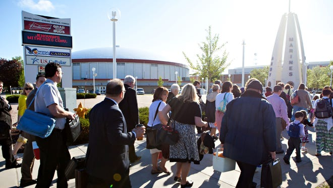 Attendees walk past Brown County Veterans Memorial Arena on their way to the Resch Center in Ashwaubenon for the Jehovah's Witnesses regional convention in 2015.