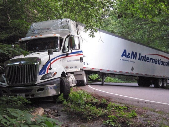 In this Aug. 18, 2015, photograph provided by the Vermont Dept. of Motor Vehicles, a tractor trailer truck blocks the road and ends up stuck in Smugglers Notch in Cambridge. State officials say truckers regularly ignore the signs when following their GPSs and get stuck. Starting July 1 truckers who get stuck are facing fines of up to $2,000 for a first offense.