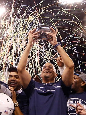 Penn State Nittany Lions coach James Franklin holds up the trophy after the game against the Wisconsin Badgers during the Big Ten Championship college football game at Lucas Oil Stadium. Penn State defeats Wisconsin 38-31.