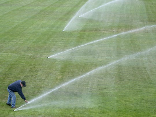 Lance McCoy checks a sprinkler at Bremerton Memorial