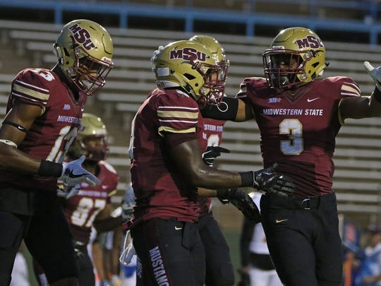 Midwestern State's Adrian Seales celebrates his touchdown against Texas A&M-Kingsville with Xavier Land (13) and Tyrique Edwards (3) Saturday, Sept. 16, 2017, at Memorial Stadium.