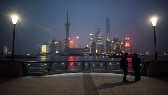 Two men stand across the Huangpu River from the Pudong New Financial district in Shanghai on Jan. 18, 2016.