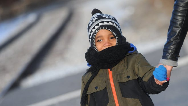 A boy is bundled up in a warm jacket, scarf and hat.