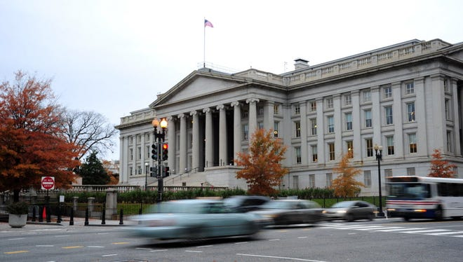 This November 15, 2011 file photo shows vehicles as they drive by the US Treasury Building in Washington, DC.