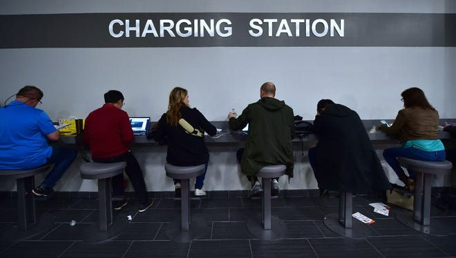 Attendees use a charging station for their mobile devices at the 2017 Consumer Electronic Show. The high-tech show is notorious for making it hard to get online and draining batteries.