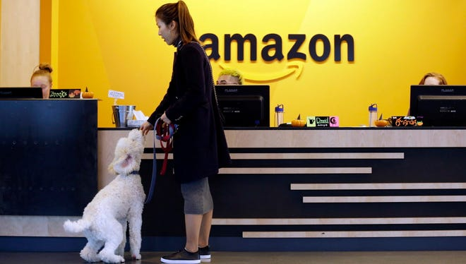 In this Wednesday, Oct. 11, 2017, file photo, an Amazon employee gives her dog a biscuit as the pair head into a company building, where dogs are welcome, in Seattle. Amazon says it received 238 proposals from cities and regions hoping to be the home of the company's second headquarters.  (Associated Press)