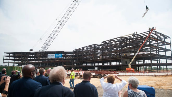 Onlookers watch as a  signed steel beam is placed into position during a topping off ceremony held at the construction site of Inspira Mullica Hill on Tuesday, May 29, 2018.  The new hospital is expected to open in late 2019.