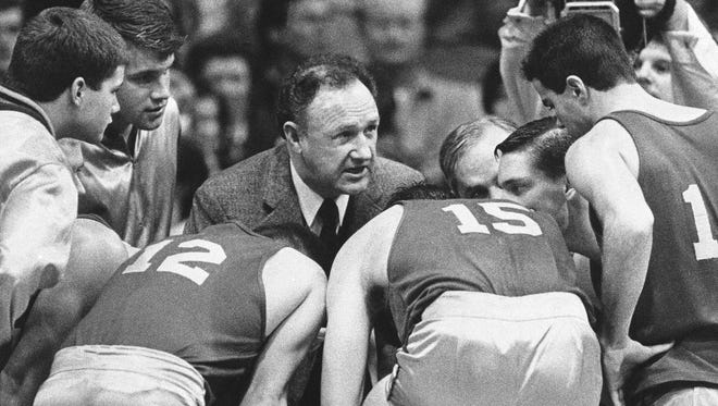"""Actor Gene Hackman gives fictional Hickory High basketball players instructions during filming of the final game of the movie """"Hoosiers"""" at Hinkle Fieldhouse on the Butler University campus, Friday, Dec. 6, 1985 in Indianapolis. About 5,000 extras jammed the start for filming after an actual high school game was moved to the field. (AP Photo/Tom Strickland)"""